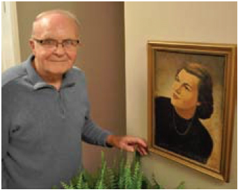 Dr. Robert Yager stands by a photo of Phyllis Yager